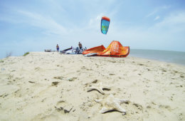 An empty idyllic paradise beach with kites in the back