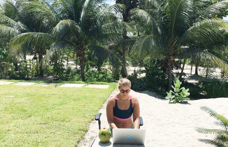 Me working on a laptop with palm trees in the beack during my kitesurf-around-the-world-trip