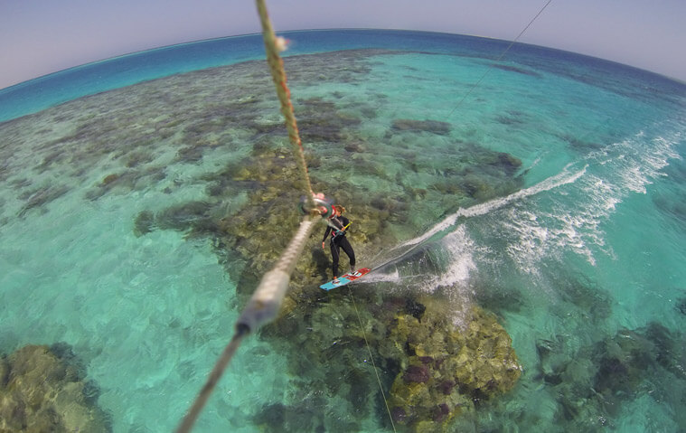 Kitesurfing over the crystal-clear reef in Hamata