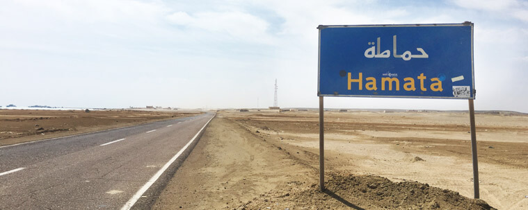 The Hamata city sign along an endless dusty road in the desert