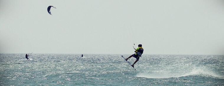 Boy jumping while kitesurfing