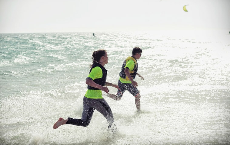 Teens running along the beach in their kitesurf outfit